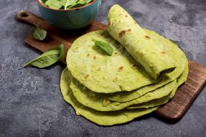 Tortillas verdi con spinaci, tortillas per impacchi, cibo messicano alla moda, concetto di snack sano su sfondo scuro
